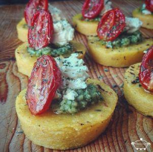 Tartine di polenta speziata con pesto di basilico, caprino e pomodorino confit
