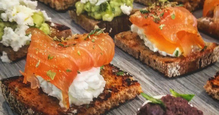 Crostino di pane nero con formaggio cremoso, salmone affumicato, miele ed origano