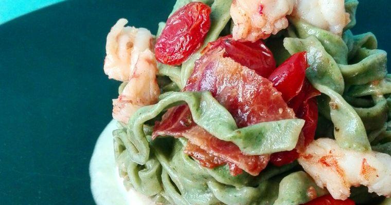 Fettuccine verdi con gamberi, bacon croccante su crema di pecorino