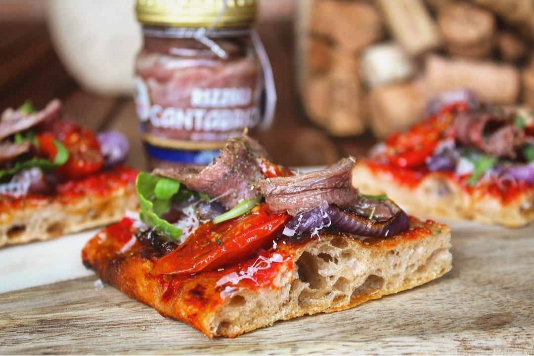 Pizza rossa con Alici del Mar Cantabrico, cipolla di Tropea, pomodorino confit, pecorino e rucola