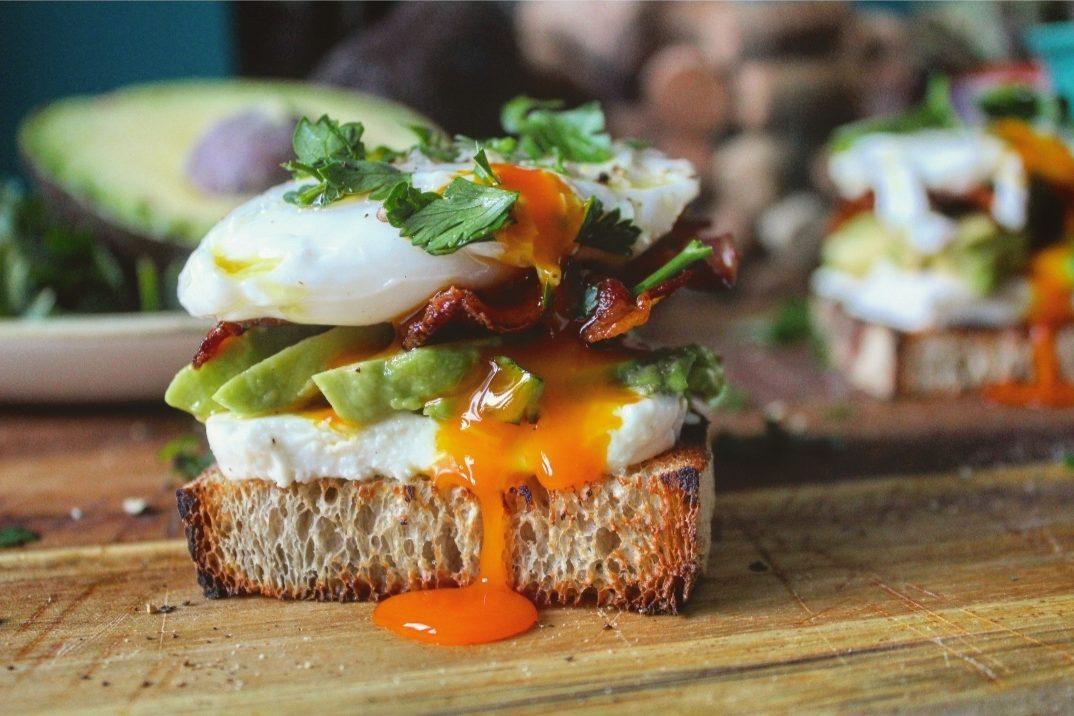 Crostone di pane con uovo pochè avocado e bacon croccante