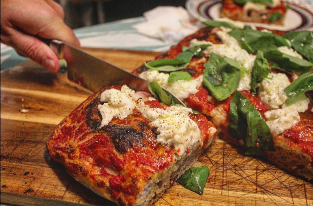 Pizza rossa con aglio in camicia, bufala e basilico
