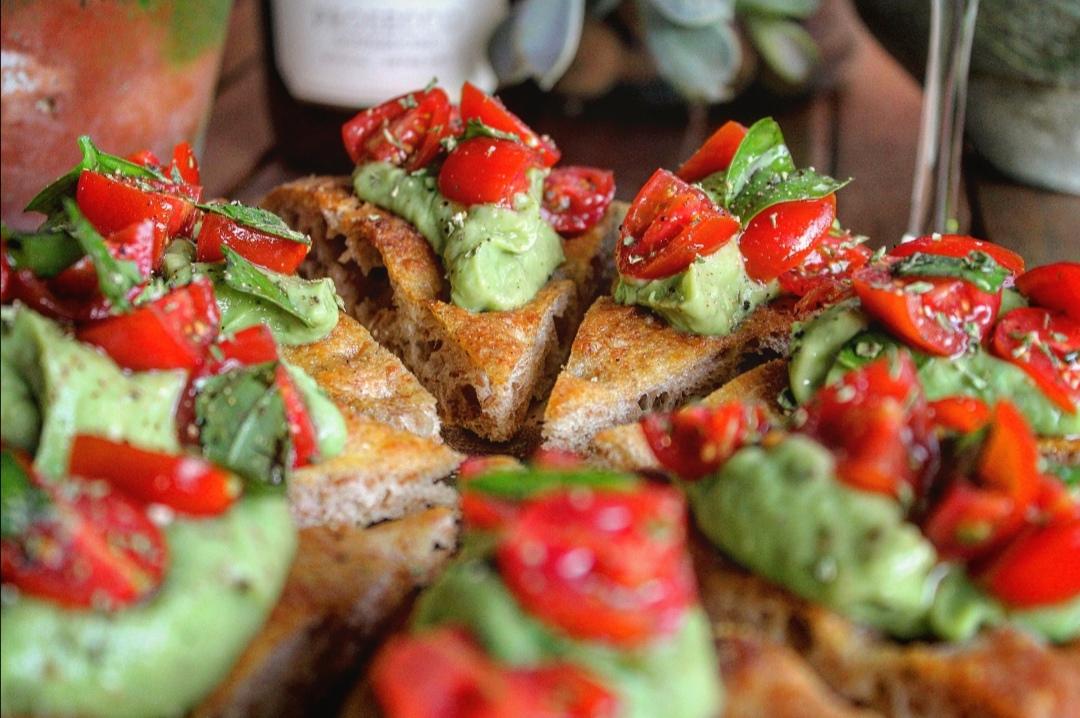 Focaccia al farro con crema di avocado pomodorini e basilico